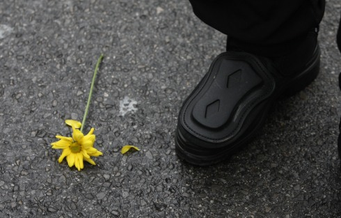 A flower laying next to the boot of a policeperson.