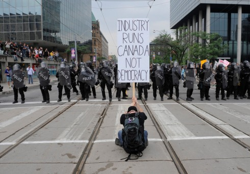 "A protestor in front of a row of riot police holds a sign saying ""Industry Runs Canada Not Democracy""."