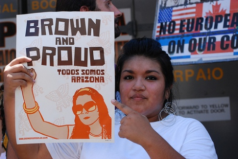 Brown and Proud sign is held by a woman at a pro-immigrant action.